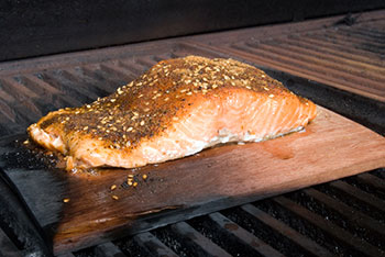 a filet of salmon roasting on a cedar plank over a fire in a wood grill