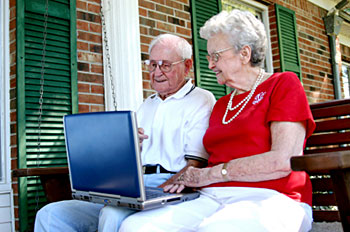 a man and woman, both seniors, sit on a bench on their front porch looking at a laptop computer held on both their laps