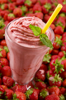 a strawberry milkshake in a tall milkshake glass garnished wtih a sprig of mint. against a background of strawberries