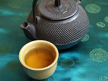 a cup of green tea next to a traditional iron teapot