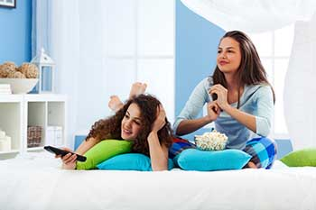 Two teens watching television and eating popcorn