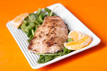 a filet of seared trout on a bed of greens, garnished with orange slices
