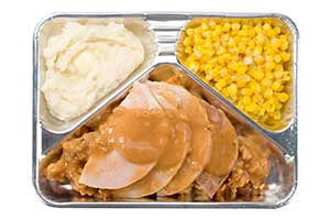 old-fashioned TV dinner in an aluminum tray: processed turkey slices with dressing, mashed potatoes, and corn