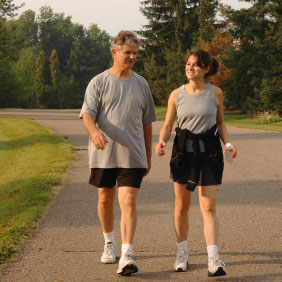 two adult persons, dressed for exercising, walking on a paved track in the outdoors