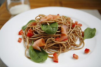 a pasta dish made with whole grain pasta, basil leaves, prosciutto, and diced tomatoes