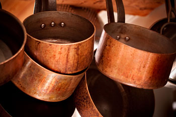 several copper pans and saucepans hanging from a rack