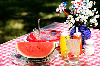 Fourth of July Table with watermelon, mustard and ketchup, and a floral centerpiece