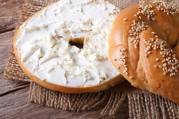 a sesame bagel sliced in half and spread with cream cheese