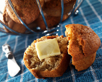 a banana nut muffin cut in half and spread with butter