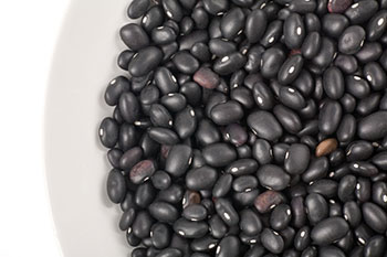 a white bowl containing dried black beans