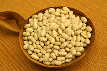dry white beans in a wooden bowl