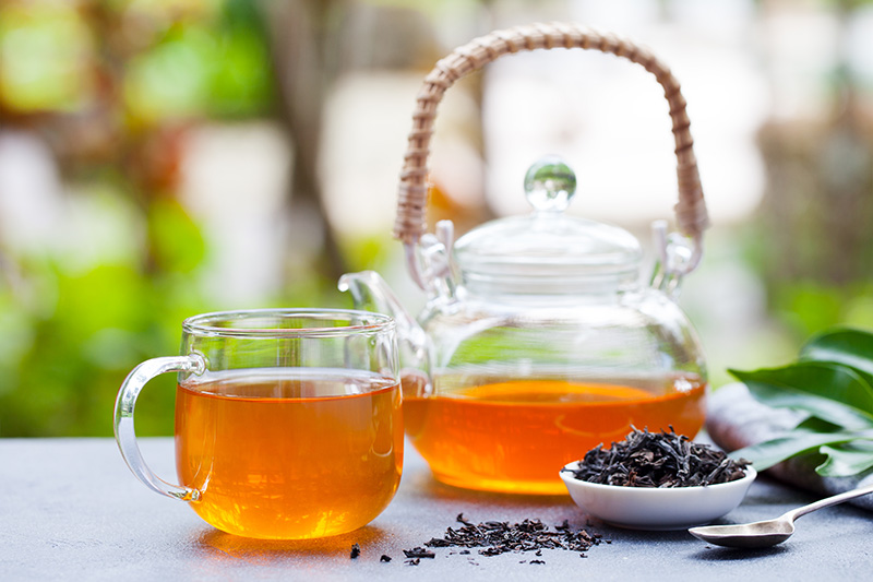 a clear glass teapot full of black tea and a glass teacup full of tea
