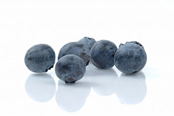 a closeup of a half-dozen blueberries against a white background