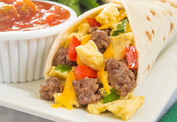 a breakfast burrito with sausage, eggs, cheese, and vegetables