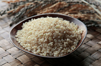 uncooked short-grain brown rice in a wooden bowl
