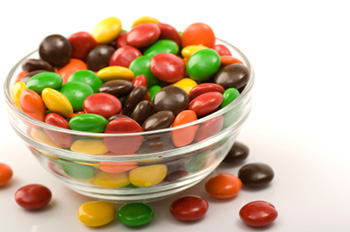 a clear glass bowl full of M&M-like candies