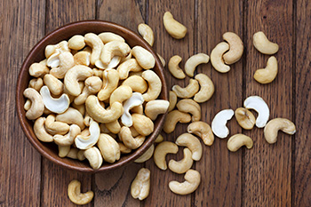 a glass bowl of cashew nuts with nuts scattered on the table in the background