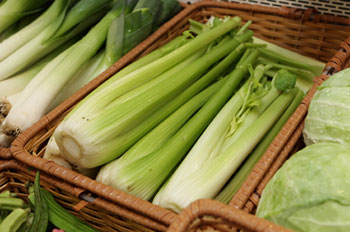 bunches of fresh celery in baskets at a farmers' market