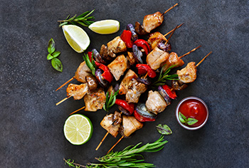 three chicken kebabs with chunks of chicken, mushrooms, and red onions