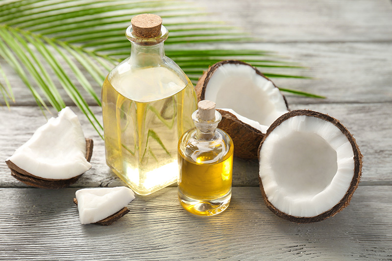 a cut-open coconut and glass containers of coconut oil