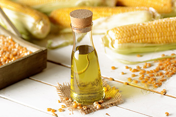 fresh corn cobs, corn kernels, and a bottle of corn oil