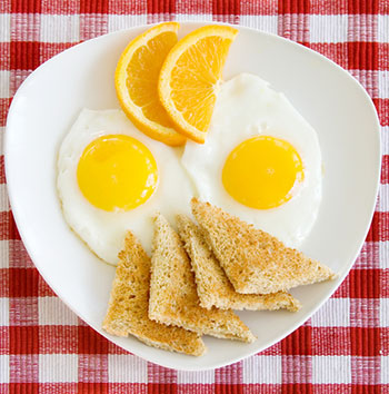 two fried eggs sunny-side-up with a piece of toast, garnished with orange slices