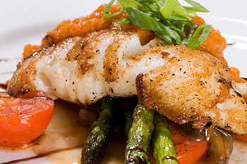 a filet of halibut on a bed of asparagus and tomatoes