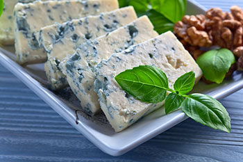 slices of gorgonzola, a type of blue cheese, on a plate with pecans and watercress garnish