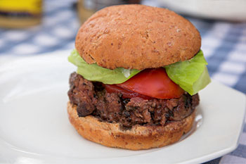 a hamburger made with beef and garnished with tomato, lettuce, and ketchup