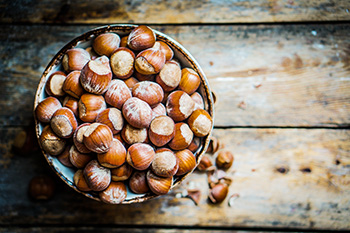 a bowl of unshelled hazelnuts