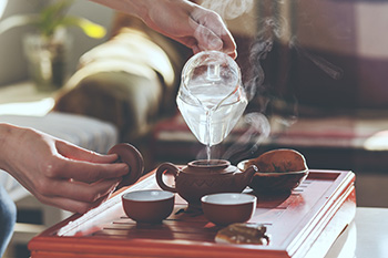 a person pours steaming hot water into an iron teapot to make green tea