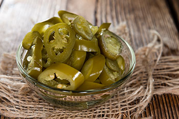 slices of pickled jalapenos in a small glass bowl