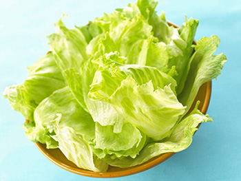 fresh, whole leaves of iceberg lettuce in a wooden bowl