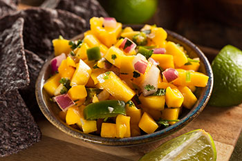 a bowl of mango salsa with blue corn chips and slices of lime on a wooden table