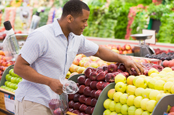 an African-American man choosing apples in the produce section of a grocery store
