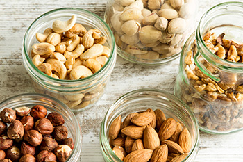 pistachios, cashews, walnuts, almonds, and hazelnuts in separate glass jars