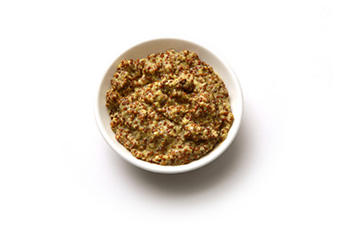 a bowl of prepared mustard containing mustard seeds.
