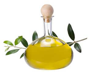 Olive oil in a cruet and olive branches as background