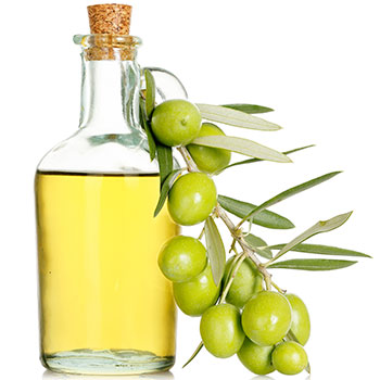 a glass bottle containing olive oil with a branch of fresh olives