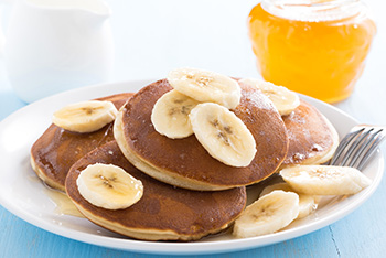 pancakes topped with fresh sliced bananas and accompanied by a glass of orange juice