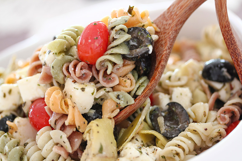 a pasta salad with rotini pasta, black olives, tomatoes, and blue cheese