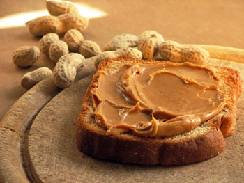 a slice of bread spread with creamy peanut butter and whole, roasted peanuts in the background