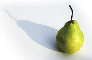 a green pear casting a shadow on a plain white table