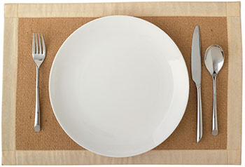 a standard place setting of fork, dinner plate, knife, and spoon