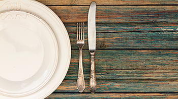 a place setting with a dinner plate, a smaller salad plate, and a fork and knife