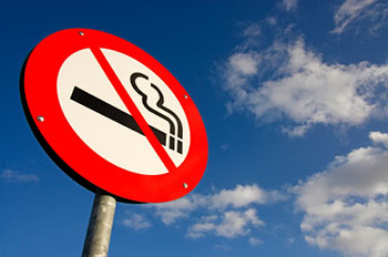 a no smoking sign against a blue sky with a few fluffy white clouds