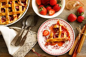 a strawberry rhubarb pie with a slice cut out of it flanked by fresh strawberries and rhubarb stalks