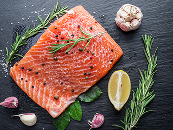 a fresh, uncooked filet of salmon, a good source of omega-3 fatty acids, on a cutting board