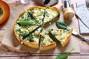 a spinach and feta cheese quiche cut into 8 slices, with 1 slice missing