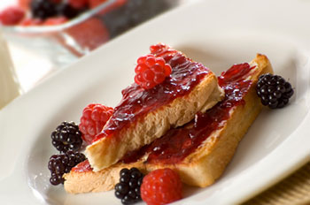 a plate of toast spread with jam along with fresh raspberries and blackberries